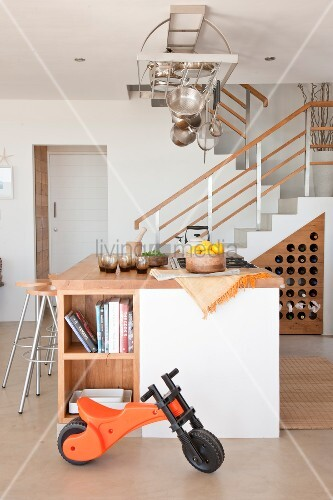 Open-plan interior with staircase and kitchen island below stainless steel pots and pans hanging from rack
