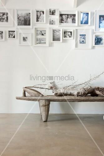 Collection of black and white photographs on white wall above driftwood lying on rustic table