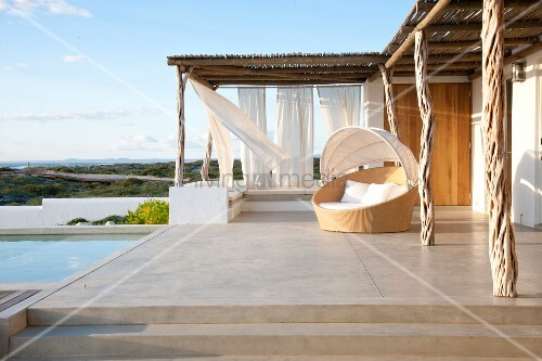 Large concrete terrace with swimming pool, circular day bed and glorious coastal view