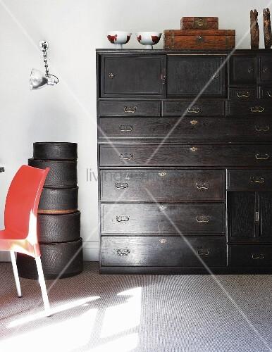 Antike, schwarze Schubladenkommode neben gestapelten Hutschachteln an weisser Wand