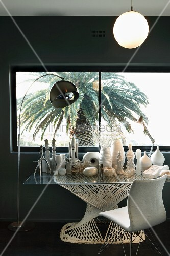 Collection of white vases and sculptures on modern glass table next to arc lamp and vintage chair in front of window with view of palm tree