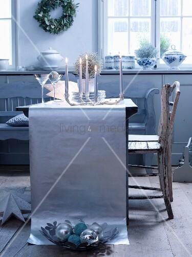 gedeckter tisch im silberlook brennende kerzen vor gl ser und teller auf tischl ufer aus. Black Bedroom Furniture Sets. Home Design Ideas