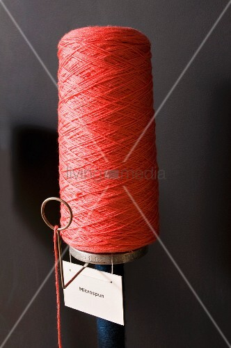 Bobbin of red yarn with label