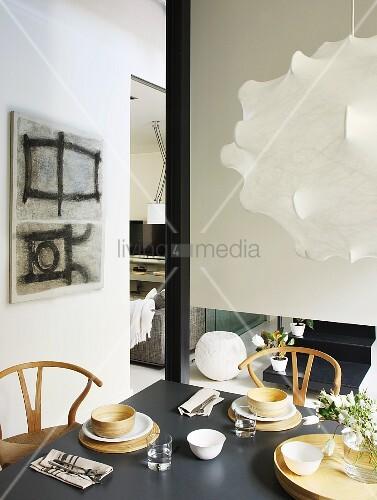 Essplatz mit 50er Jahre Klassikerstühlen und textilbespannter Designerlampe