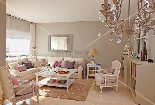 Beige Getöntes Wohnzimmer Mit Traditionellem Überecksofa Und Sesseln Im  Antikstil, Kronleuchter Im Vordergrund