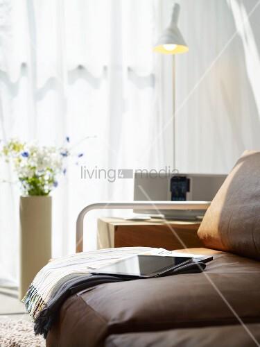 ledercouch mit wolldecke tageszeitung und ipad holzblock als tisch mit ipod anlage stehlampe. Black Bedroom Furniture Sets. Home Design Ideas
