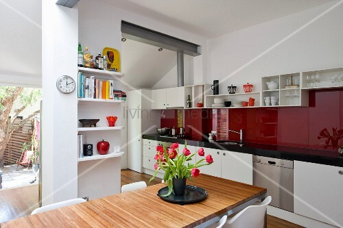 Bouquet of tulips on dining table in modern kitchen with long kitchen counter and red glass splashback