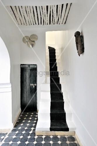 Verschmelzung von marokkanischer Tradition und Moderne in schwarzweiss gestaltetem Vorraum mit schmalem Treppenaufgang