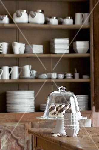 Tortenständer mit Glashaube auf Tisch vor Vintage Geschirrschrank mit weißem Porzellangeschirr