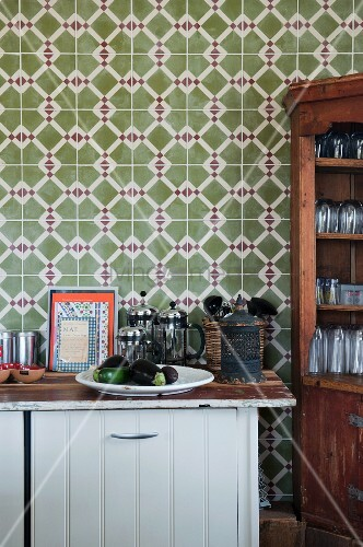 Half-height cupboard and partially visible dresser against wall with patterned tiles