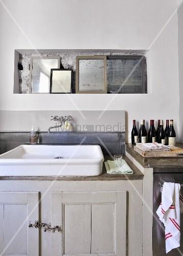 Wandnische mit Spiegelsammlung über Vintage Spülbecken und grauer Unterschrank in schlichtem Ambiente