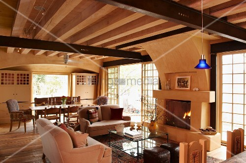 Pale sofa set and glass coffee table in front of open fireplace in rustic house with wood-beamed ceiling and single pendant lamp with blue lampshade