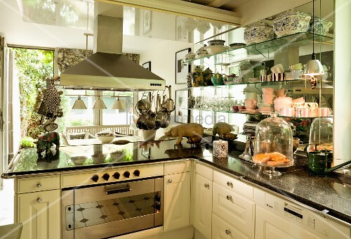 Moderne Küche Im Landhausstil Mit Dunstabzug Und Geschirrsammlung Auf  Seitlichen Glasregalen; Kleine, Freundliche Keramikschweine Auf Der ...