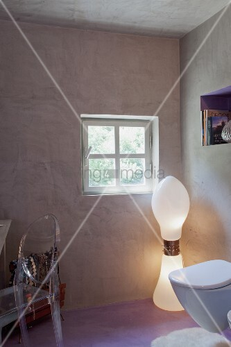 Postmodern inspired bathroom with designer lamp and acrylic chair with concrete walls and pastel violet floor