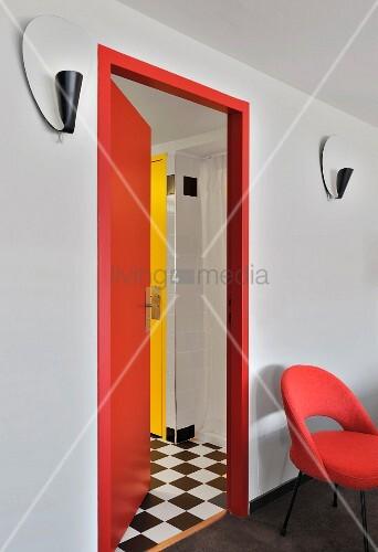 roter gepolsterter stuhl an wand neben offener roter t r und blick in vorraum mit schwarz. Black Bedroom Furniture Sets. Home Design Ideas