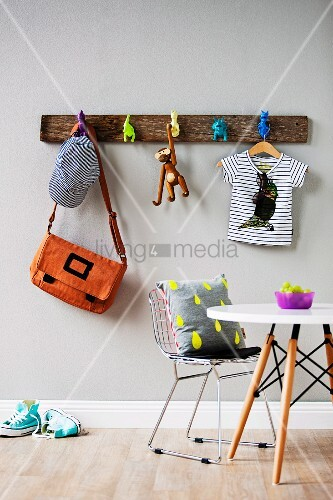 Rustic wooden coat rack on wall with hooks made from toys; table and Bauhaus chair