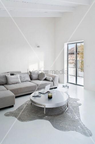 Puristisches Wohnzimmer in Grau/Weiss mit Designertisch auf Tierfell und Überecksofa