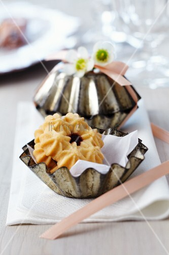 Small cake moulds filled with biscuits as guest favours