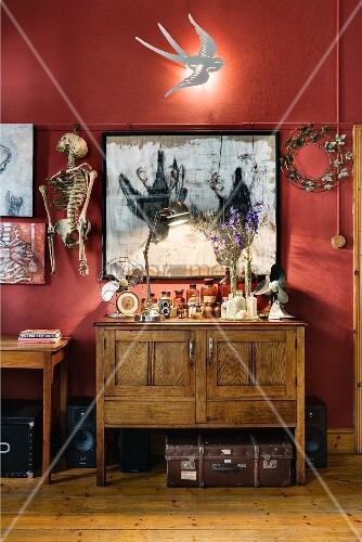Swallow-shaped sconce lamp on wall above collection of bizarre objets d'art and vintage cabinet