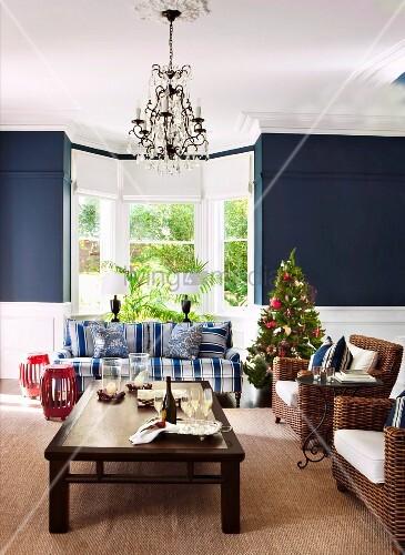 Kleiner Weihnachtsbaum zwischen blauweiss gestreiftem Sofa und Korbsesseln vor Wohnraumerker mit blau getönten Seitenwänden