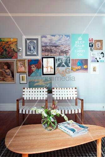 Armlehnstühle mit Gurtgeflecht und Nierentisch mit bunt gemixter Bildergalerie im Hintergrund