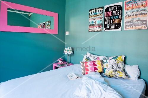 bett mit bunten kissen unter pinkgerahmtem spiegel und bildern mit englischen spr chen vor. Black Bedroom Furniture Sets. Home Design Ideas