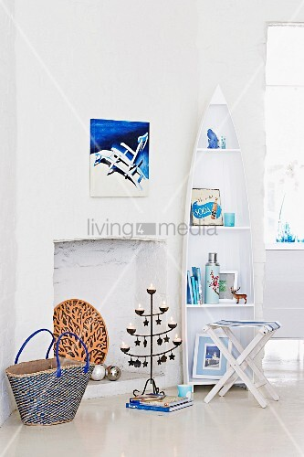 White, boat-shaped shelving, folding chair and metal candlestick in front of fireplace