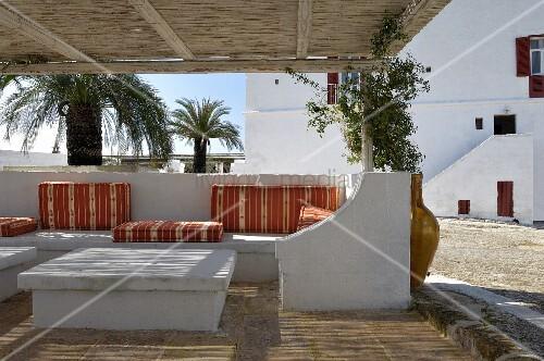 Überdachte Terrasse mit gemauerten Möbeln und weichen Sitz- und Liegepolstern