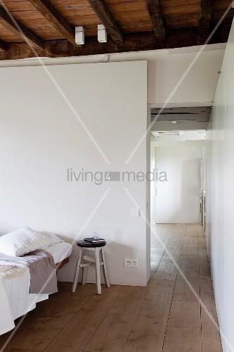 Einfacher Holzhocker als Nachttisch neben einem Bett; Blick durch türlosen Durchgang in angrenzendem Raum