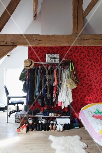 Jugendzimmer unter sichtbarem Dachstuhl mit Kleiderstange und offenem Schuhregal vor gemusterter Wandgestaltung