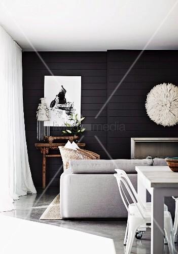 Moderner Wohn-Essbereich in weiß vor schwarzer Holzverkleidung mit weissem Deko Wandschmuck über Kamin und antikem Tischchen