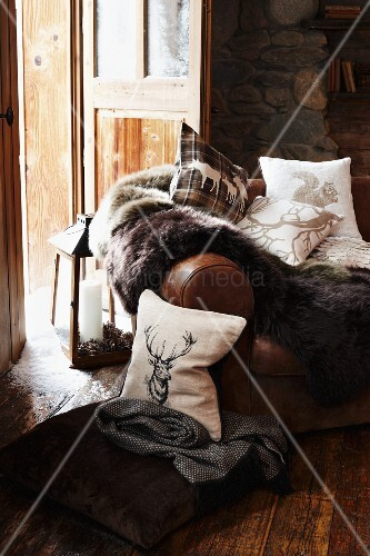 Leather sofa with a throw and pillows in a traditional chalet