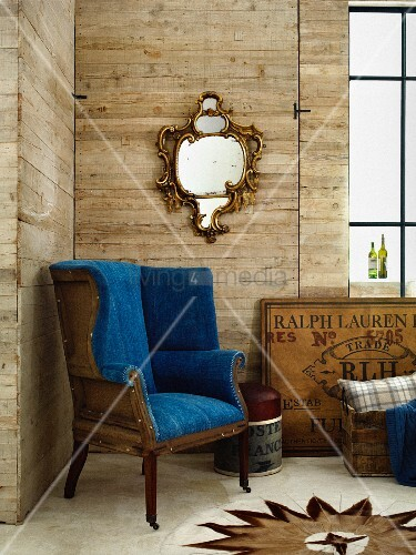 Designer armchair with royal blue cover and Italian, 19th century mirror in corner of room with wooden walls
