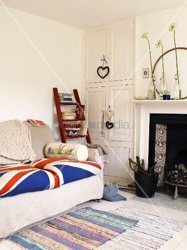 Sofa mit Union Jack Motiv und Holzleiter mit Büchern neben weißem Einbauschrank