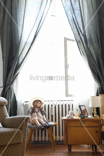 Eine Puppe sitzt auf einem Hocker zwischen Sessel und Nachttisch vor dem Fenster