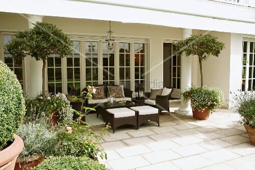 Braune Outdoormöbel auf Steinboden einer Terrasse mit Säulen und ...