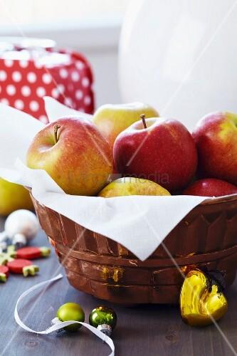 Backform als Ostkorb mit Äpfeln und weihnachtlicher Dekoration