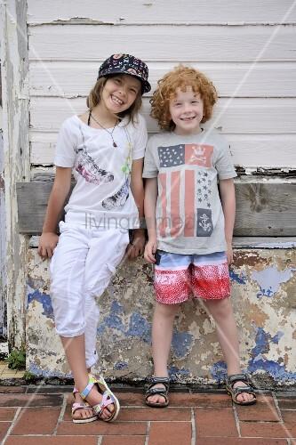 Zwei Kinder lehnen an verwittertem Steinsockel eines alten Holzhauses