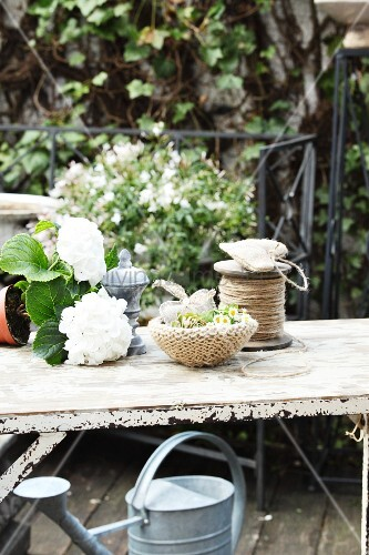 White hydrangea next to dish with hand-knitted cover and reel of yarn on vintage garden table