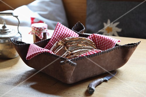 Red and white gingham napkin and sliced bread in rustic bread basket of stitched leather