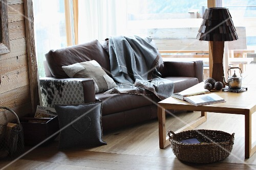 Modern, country-house atmosphere in seating are with hand-sewn cushions and blanket on leather sofa