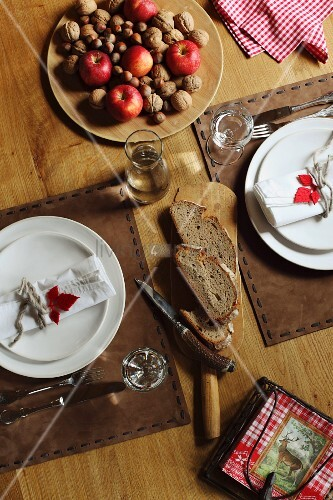 Festive place settings with decoratively stitched leather place mats; plate of apples and nuts