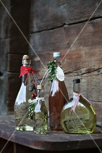 Mit Ornament, Anhängern und Bändchen als Geschenk verzierte Flaschen mit Sekt und Wein