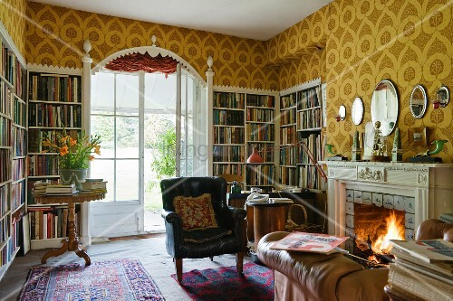 Bookcases built into niches and lounge chair in front of open fire in study of English country manor house