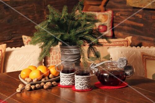 Teegläser und Tannenzweig Vase mit Strickhülle neben Teekanne und adventlicher Schale auf Holztisch einer Holzhütte