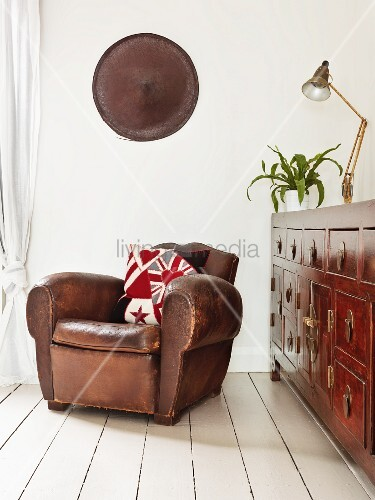 Vintage leather armchair next to antique chest of drawers on white wooden floor