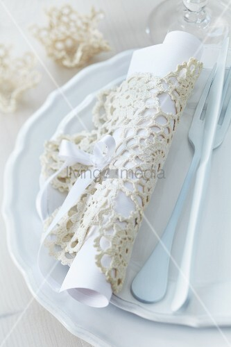 Menu rolled up in crocheted doily and cutlery on set of plates