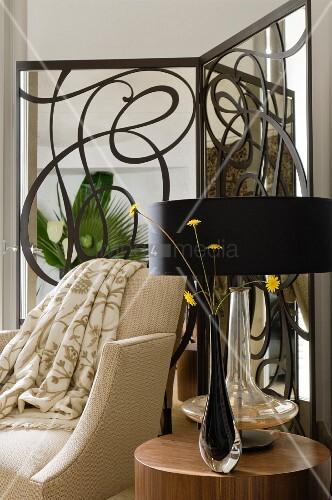 Schwarze Glasvase mit Blumen und Tischleuchte mit schwarzem Schirm auf Beistelltisch vor hellem Sessel und moderner, schmiedeeiserner Paravent