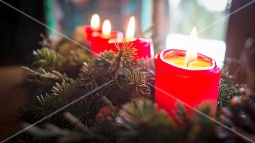 Adventsgesteck mit brennenden Kerzen