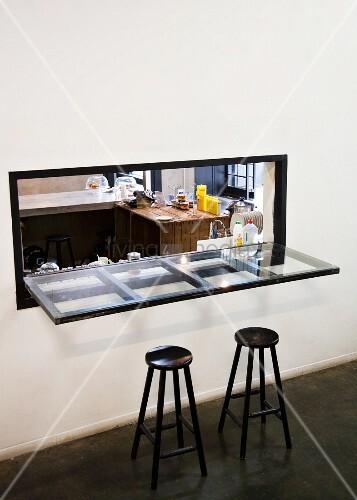 Durchreiche Küche schwarze barhocker vor glasplatte als tischfläche in durchreiche mit